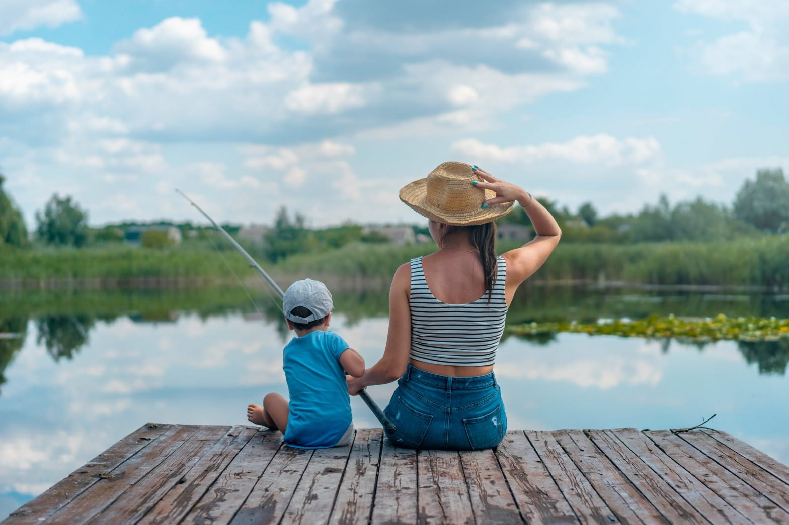 Woman and young son sitting on a wooden dock, fishing