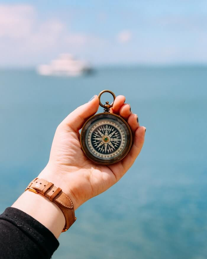 Person holding a compass in front of open waters with a white boat in the background.