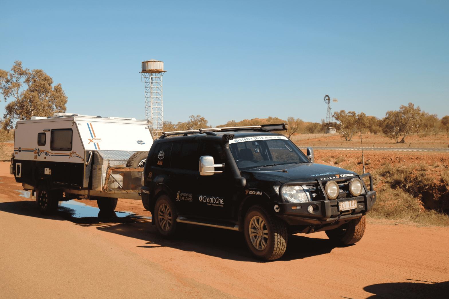 Black 4WD towing a caravan