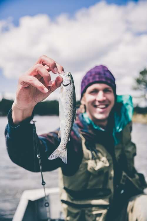 Man smiling and holding a freshly caught fish.