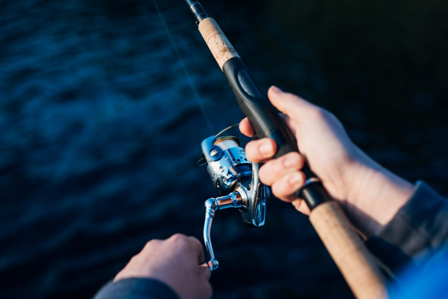 Close up of rod and reel as person fishes into deep blue waters.