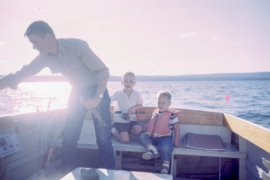 Father fishing with his children on a small boat at sunset